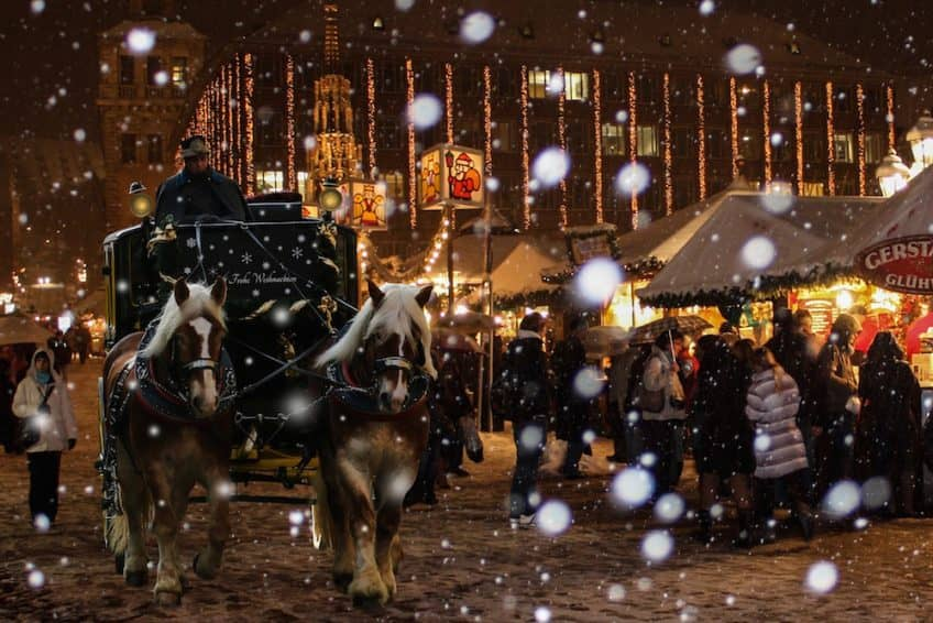 A horse-drawn cart passes a Christmas market in the snow