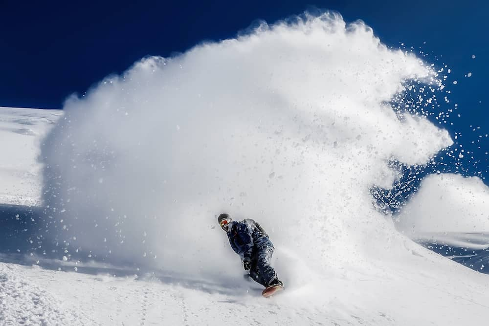 Snowboarder creates a snow wave