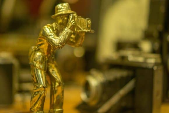 A gold antique miniature statue of a man taking a photograph with a vintage camera