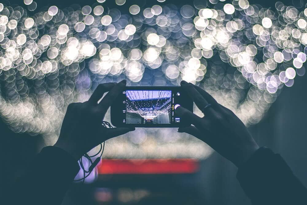 Image of two hands holding a smartphone, about to take a photograph of a picturesque scene of colourful lights.
