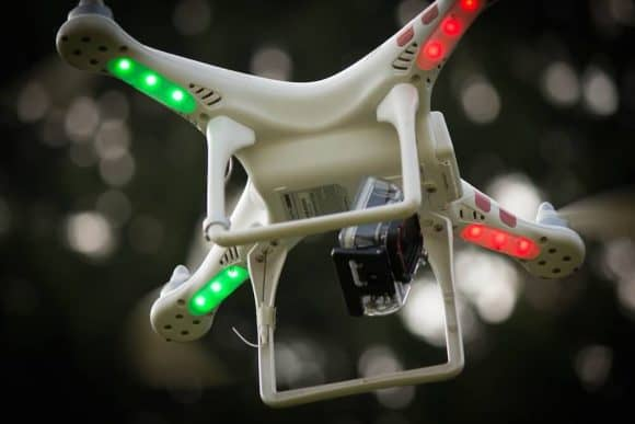Low-angle shot of a drone in flight with a camera affixed to its body.