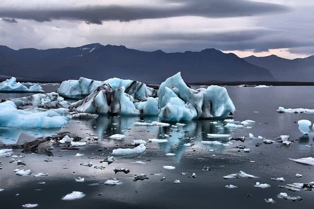 A cluster of floating glaciers with a stormy weather backdrop.
