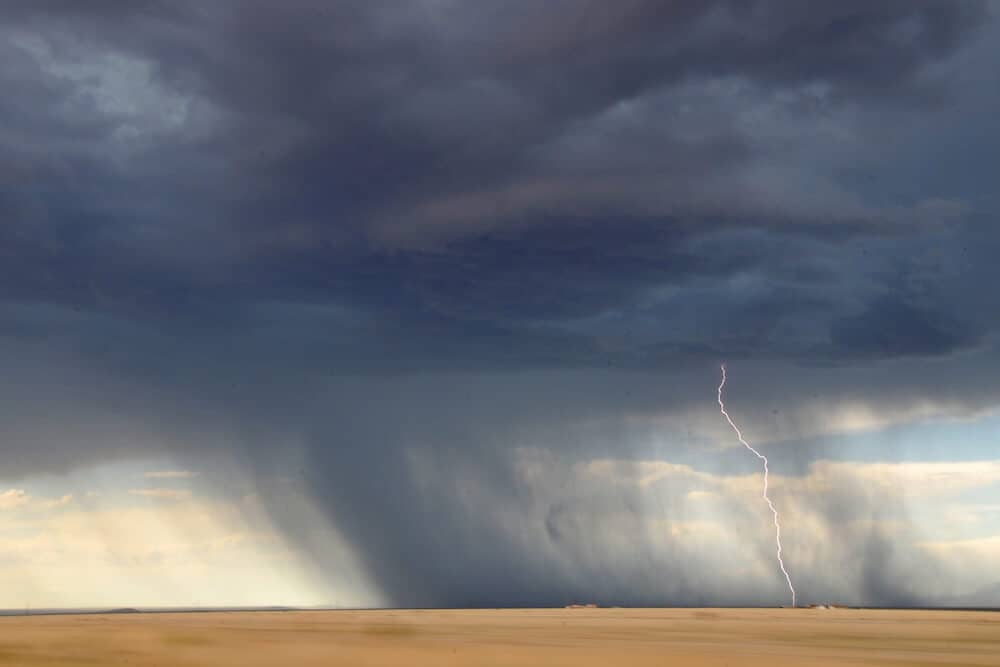 Lightning and storm clouds over a desolate landscape.