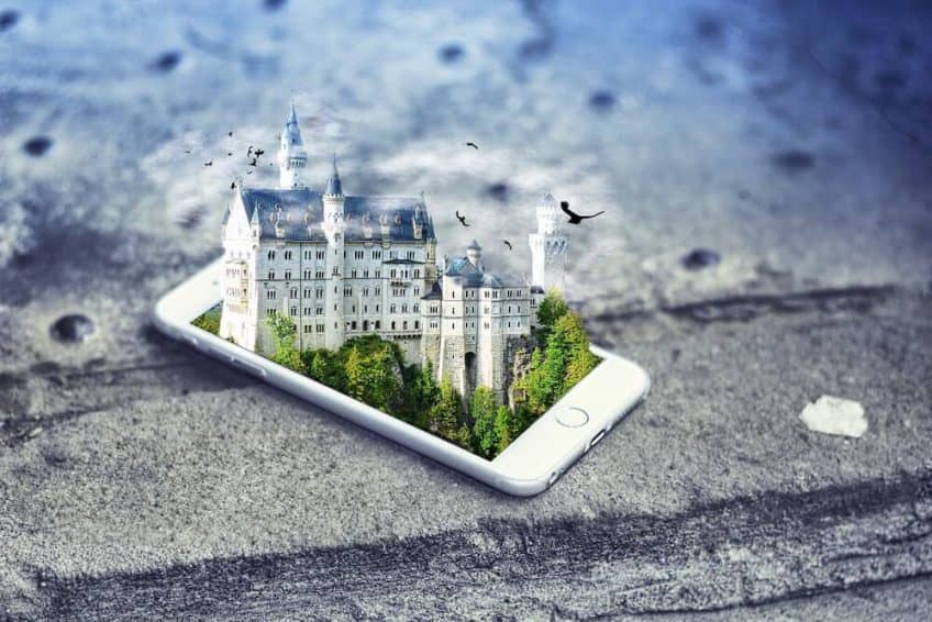 An idyllic castle emerging from the screen of an iPhone - depicting a virtual reality.