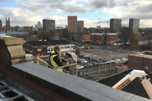 Engineer manning a cherry picker on a rooftop overlooking Manchester.
