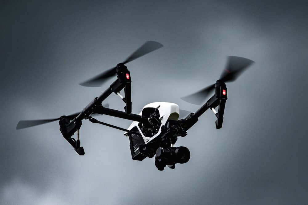 A drone in flight in cloudy skies.