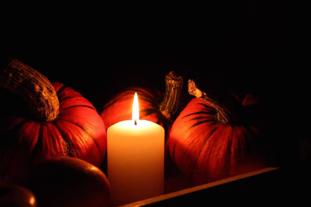 Pumpkins in the darkness lit by a lone candle.