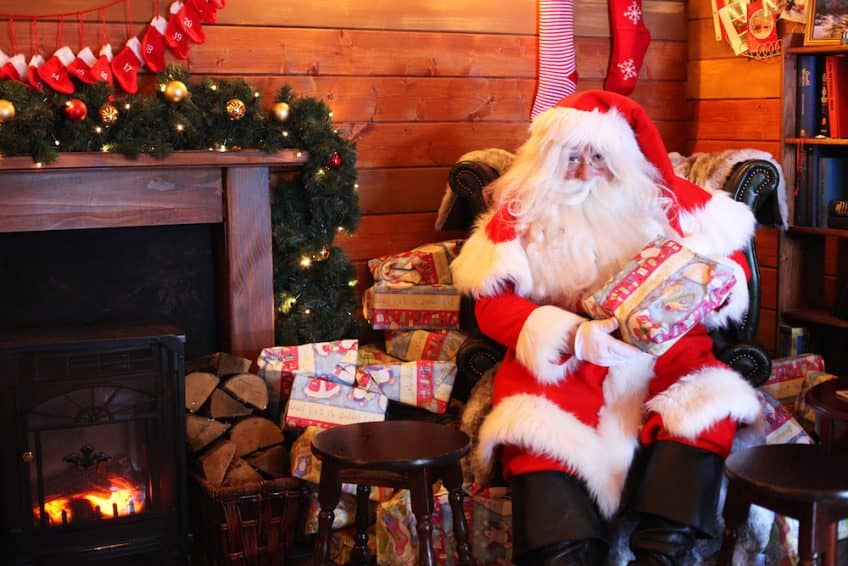 Santa sitting in front of the fireplace.