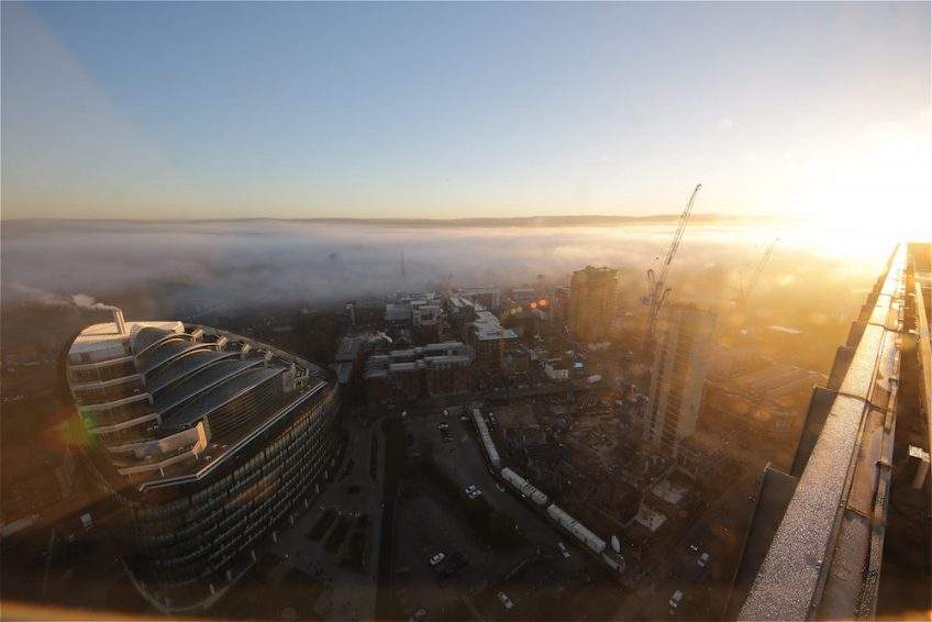 Early morning sun illuminating a sheet of fog sitting on Angel Gardens, Manchester.
