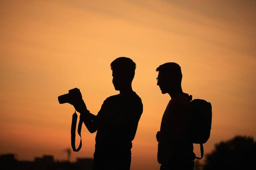Silhouette of two photographers in front of the LA sunset.