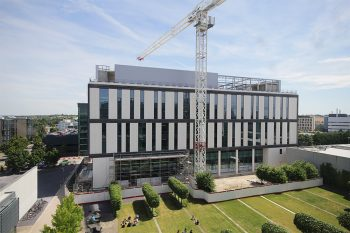 A Kier crane overhangs the completed Project Capella Building at the University of Cambridge Biomedical Campus