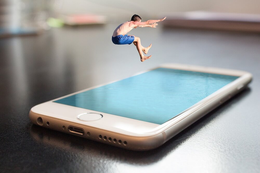 Photo manipulation of a child jumping into a smartphone screen.