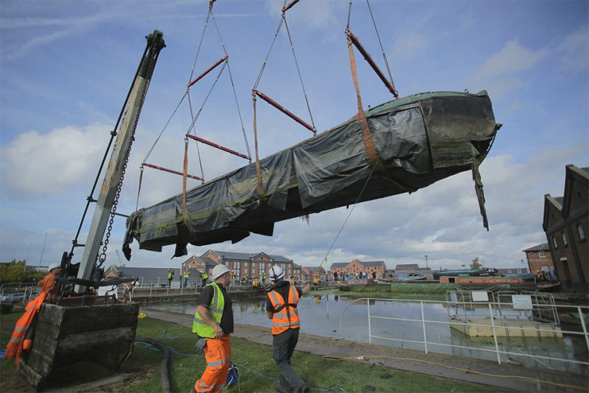 A watercraft being lifted from the dock at Ellesmere Port for transportation to restoration workshop nearby