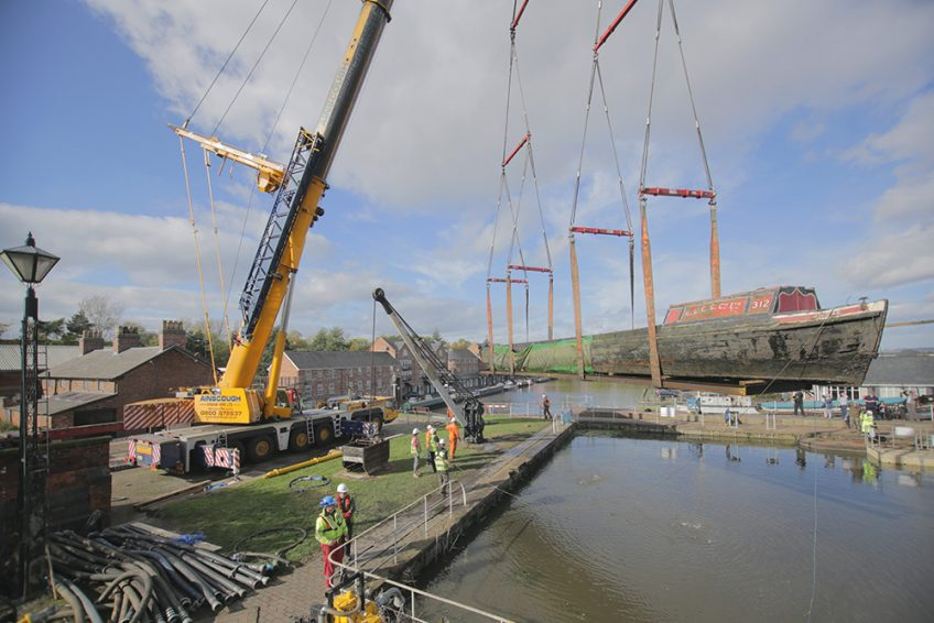Historic inland waterways craft being craned out of dock at Ellesmere Port
