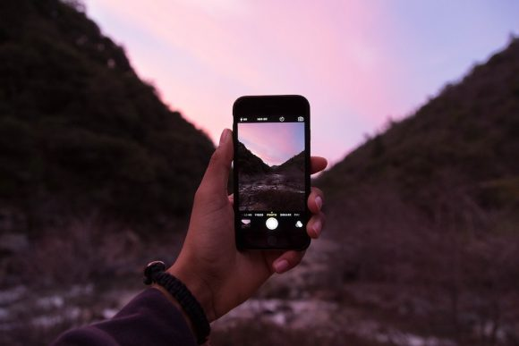 A smartphone pictured capturing a natural scene.
