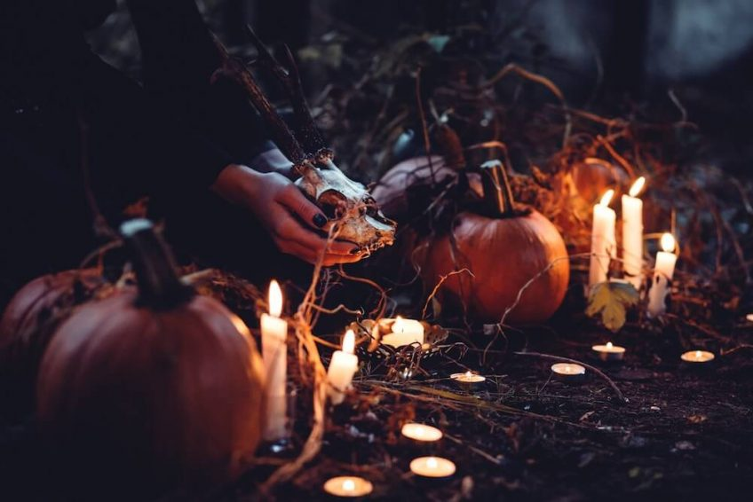 A low-lit Halloween-themed scene featuring iconic seasonal items, such as pumpkins, candles and skulls.