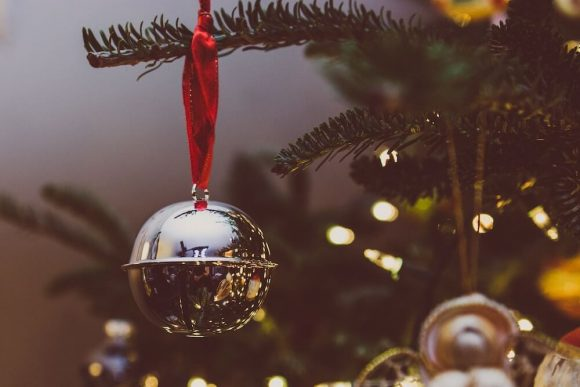 Bokeh reflections on a grey and red Christmas tree bauble.