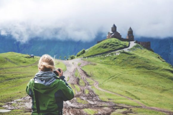 Woman holding a camera taking a photograph of a castle on a green hill.