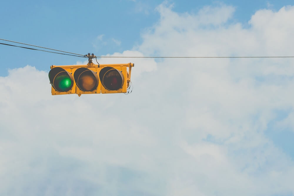 Yellow traffic light sign on green in front of blue skies.