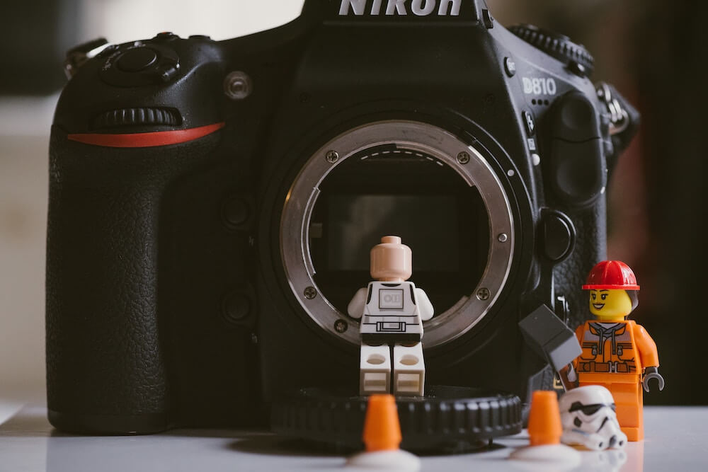 Lego minifigures photographed beside a Nikon DSLR camera.