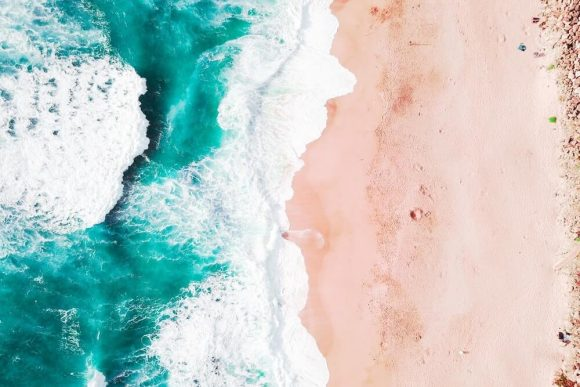 Aerial perspective of waves crashing onto a sandy beach.